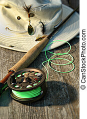 Close-up of fly-fishing reel and rod with hat - Close-up of...