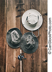 Fishing hats and pole against wood wall