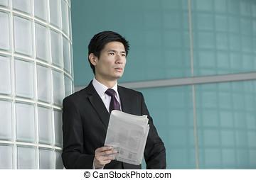 Asian businessman holdiung newspaper.