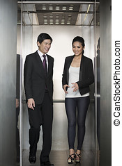 Two happy Asian business colleagues walking out of lift -...