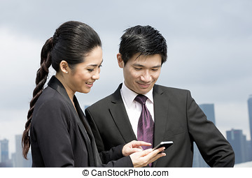 Chinese business people using smart phone - Two Chinese...