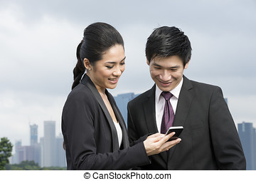 Chinese business people using smart phone. - Two Chinese...