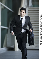 Asian businessman running through city - Young Chinese...