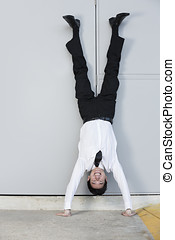 Chinese Businessman doing handstand outdoors. Conceptual...