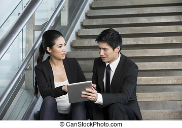 Asian Businessman and woman using tablet. - Happy Chinese...