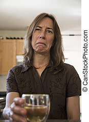 Unhappy Middle Aged Woman in the Kitchen Drinking Wine -...