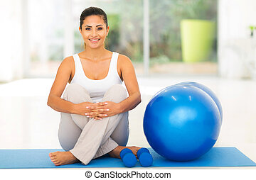 woman sitting on mat with exercise ball - gorgeous young...