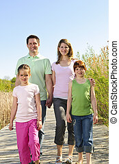 Happy family - Portrait of happy family of four walking on...