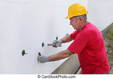 Construction site, styrofoam insulation - Worker placing...