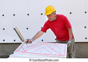 Construction site, styrofoam insulation - Worker applying...
