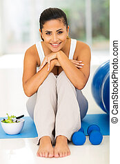 happy woman resting on mat after exercise - happy young...