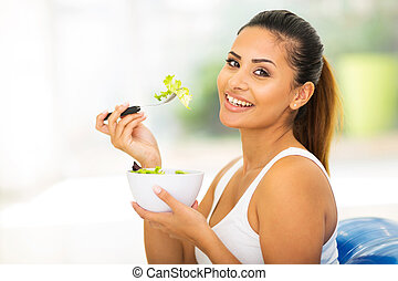 pretty woman eating healthy food at home