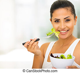 young woman eating green salad - beautiful young woman...