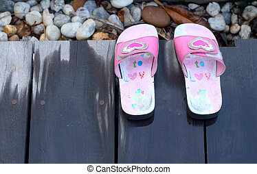 Pink children shoes at the pool.