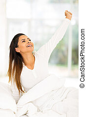 young woman getting up in the morning and stretching