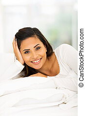 pretty woman lying in cozy bed relaxing