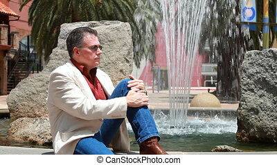 Man Sitting at the Fountain - A man relaxing by the...