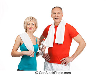 pretty man and woman standing in gym aged lady holding water...