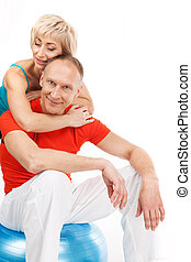 beautiful blond lady hugging aged man. male sitting on fitness ball and smiling