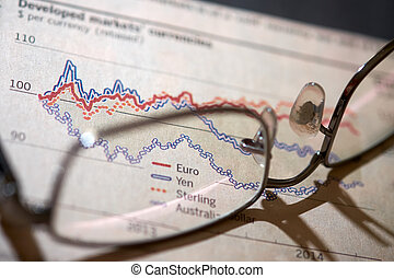 Stocks and shares Trading. Pair of glasses on top of a...