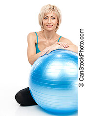 blond lady sitting behind fitness ball aged woman resting...
