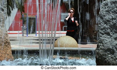 Woman on phone through fountain - Water cascading from a...