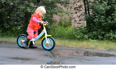Little Girl on Bicycle on wet Street with Puddles
