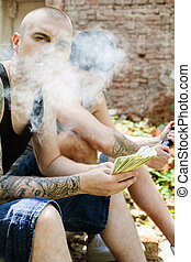 criminal smoking cigarette and counting money. two gangsters sitting with brick wall on background
