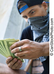 close up of criminal man holding money. gangster sitting outside and counting money
