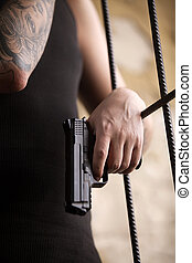 gangster man standing and holding gun. closeup of gun in...