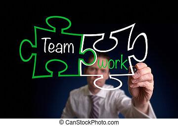 Teamwork - A Businessman drawing a Teamwork puzzle concept.