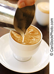 A barista creating latte coffee art - A barista creating a...