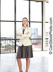 Serious businesswoman standing in an office looking at the...