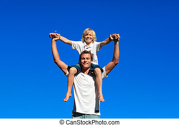 Son sitting on his fathers shoulders - Happy son sitting on...