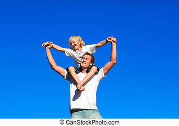 Youth sitting on his fathers shoulders - Smiling youth...