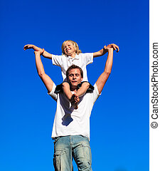 Dad giving his son a piggyback ride against the blue sky