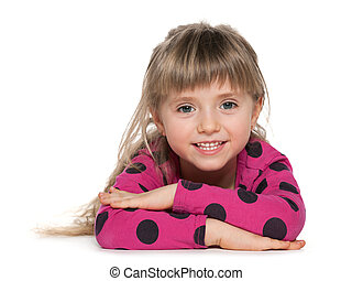 Smiling little girl is lying on the white