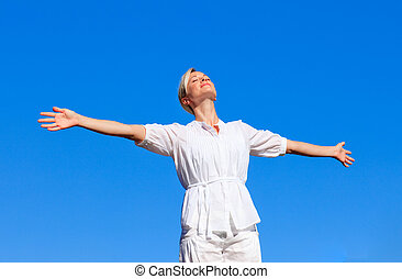 Happy woman with open arms outdoors