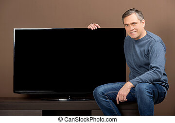 older man sitting and holding tv set. guy with grey hair on...