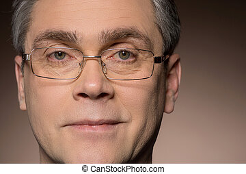 closeup portrait of man wearing glasses. man with glasses smiling isolated on brown background