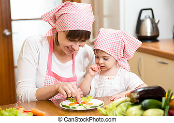 mother and kid girl making funny face from vegetables on...