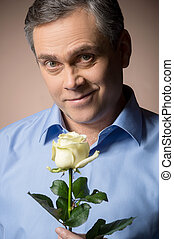 man holding white rose and smiling. closeup portrait of man...