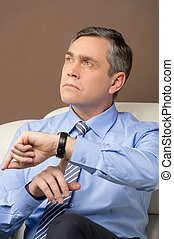 closeup of older man looking at watch portrait of...