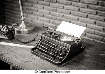 Black and white of an old typewriter with paper on a wooden...