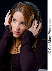 portrait of young woman listening music through headphone