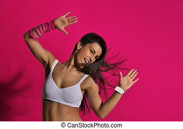 beautiful fitness woman dancing, against the pink background