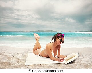 Summer relax - Beautiful girl reads a book on the beach