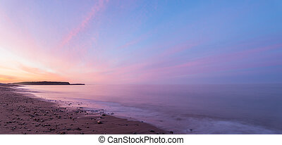 Panorama of ocean beach at the crack of dawn - Panorama of...
