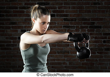Young fit woman lifting kettle bell - Portrait of Young fit...