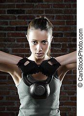 Young fit woman lifting kettle bell and looking at camera -...